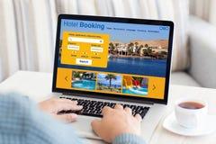 供以人员键入在有旅馆预定屏幕室的膝上型计算机键盘 免版税库存照片