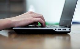 供以人员键入笔记本键盘的` s手 库存照片