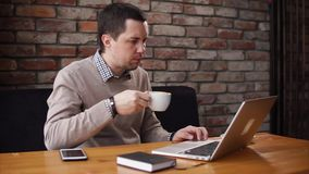 供以人员饮用的咖啡和与在咖啡馆的膝上型计算机一起使用 股票视频