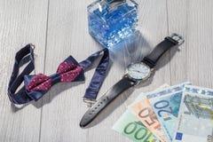 供以人员香水、手表有黑皮带的,蝶形领结和欧元 免版税库存图片