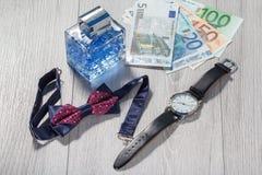 供以人员香水、手表有黑皮带的,蝶形领结和欧元 库存图片