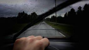 供以人员驾驶在公开路的一辆汽车在与水滴的重的降雨量期间在挡风玻璃和橡胶刮水器 免版税图库摄影