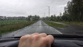 供以人员驾驶在公开路的一辆汽车在与水滴的重的降雨量期间在挡风玻璃和橡胶刮水器 图库摄影