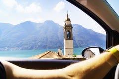 供以人员驾驶在Como湖,意大利的一辆汽车 被打开的窗口、湖视图和一个老教会 库存照片