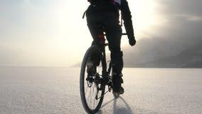 供以人员骑横跨一个冻湖的一辆自行车 影视素材