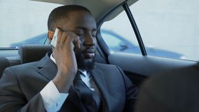 供以人员骑马在汽车后座,谈话在被注重的手机,婚姻问题 股票录像