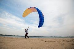 供以人员,与被聚焦的面孔,控制风筝,滑翔伞 图库摄影
