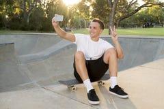 供以人员30s坐冰鞋板在体育搭乘拍selfie照片画象或照片在手机的训练以后 库存照片
