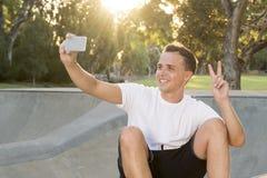 供以人员30s坐冰鞋板在体育搭乘拍selfie照片画象或照片在手机的训练以后 库存图片