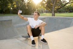 供以人员30s坐冰鞋板在体育搭乘拍selfie照片画象或照片在手机的训练以后 免版税库存图片
