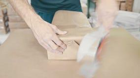 供以人员` s手包装盒在印刷业,顶视图的sellotape 股票视频