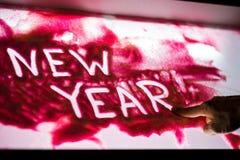 供以人员` s手指图画`新年在明亮的桃红色沙子的`词 图库摄影