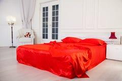 供住宿与在白色卧室内部的红色板料 免版税库存图片