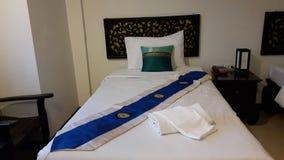 供住宿与白色卧具,装饰用枕头和蓝色床赛跑者 免版税库存照片