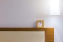 供床头板、白色枕头、小时钟和顶上的灯住宿, 免版税库存图片