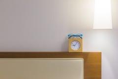 供床头板、镜片、小时钟和顶上的灯住宿, 库存图片
