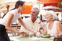 供应资深夫妇午餐的女服务员在室外餐馆 库存照片