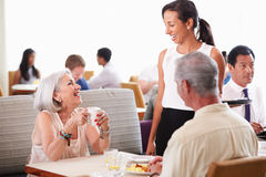 供应资深夫妇早餐的女服务员在旅馆餐馆 免版税库存照片