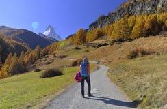 供徒步旅行的小道和秋天场面的女孩在有马塔角山的策马特在背景中 免版税库存照片