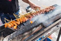 供营商准备鸡的和牛肉烤satay在木炭gri 库存图片