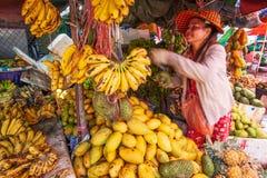 供营商卖香蕉的高棉妇女是成熟,芒果和其他tr 免版税库存图片