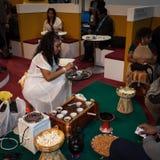 供食传统咖啡的埃赛俄比亚的妇女在位2014年,国际旅游业交换在米兰,意大利 免版税库存图片