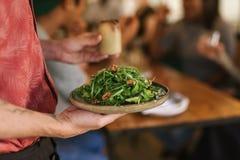 供食健康沙拉的侍者对餐馆顾客 免版税库存照片