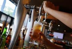 供食冷的压力啤酒的女服务员 免版税图库摄影