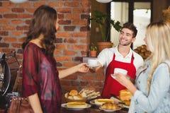 供食咖啡的微笑的侍者对顾客 库存图片
