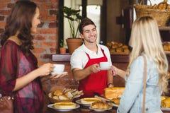 供食咖啡的微笑的侍者对顾客 免版税库存照片