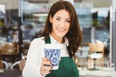 供食咖啡的微笑的女服务员 免版税库存照片