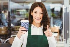 供食咖啡的微笑的女服务员 免版税图库摄影