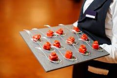 供食咸小开胃菜的头脑在红色釉的侍者装饰用各式各样的蕃茄和microgreens 免版税库存照片