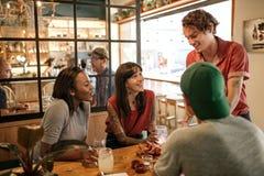 供食新近地做的食物的微笑的侍者对餐馆顾客 免版税库存图片