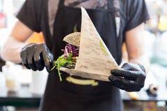 供食有机素食鱼汉堡的厨师在国际都市街道食物节日 库存图片