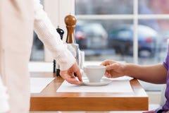 供食杯子pf咖啡的女服务员 库存照片