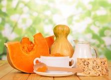 供食汤用南瓜,水罐牛奶,在抽象绿色的曲奇饼 免版税图库摄影