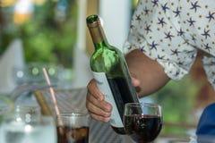 供食红葡萄酒的侍者在餐馆 库存图片