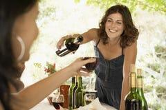 供食红葡萄酒的妇女对党的女性朋友 免版税库存图片