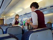 供食食物的空服员对乘客在飞行期间 库存照片