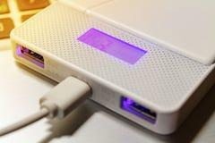 供给与USB连接的银行充电的过程动力与膝上型计算机 图库摄影