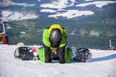 供以人员一个倾斜的挡雪板在冬天山 免版税图库摄影