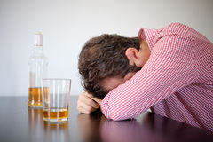 供以人员上瘾酒精供以座位的孤独在威士忌酒glas前面 库存图片