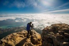 供以人员与一台三脚架和照相机的身分在云彩、城市和海上的一个高山峰顶 专业摄影师 免版税图库摄影