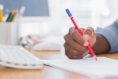 供以人员与一支红色铅笔的图画在书桌上 免版税库存照片