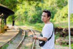 供以人员与数字式片剂和袋子等待的火车的身分 免版税库存图片