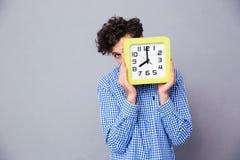 供以人员与时钟的覆盖物面孔和看照相机 免版税库存照片
