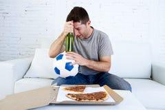 供以人员举办球和啤酒瓶观看的橄榄球赛在电视丧气的哀伤和失望为失败或失败 免版税库存照片