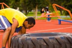 供以人员举大拖拉机轮胎的佩带的黄色衬衣和蓝色短裤在力量锻炼期间,户外训练 免版税图库摄影