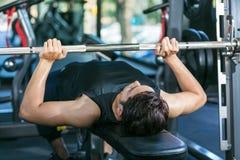 供以人员举的哑铃重量,当躺下在健身房时 免版税库存图片